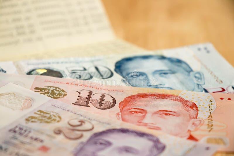 Накрените банковская книжка на предъявителя с долларом Сингапура на деревянной таблице стоковая фотография