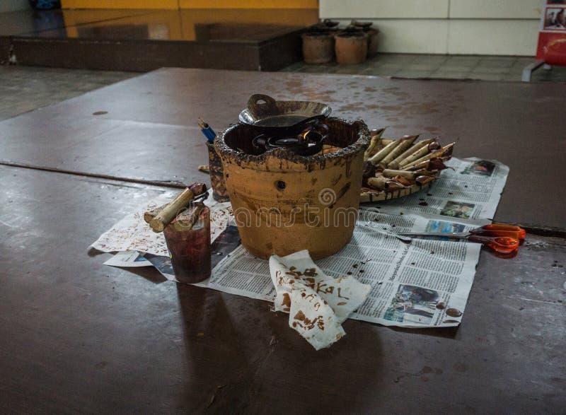 Наклоняя и горячий воск na górze деревянной таблицы для батика обрабатывая фото принятое в Pekalongan Индонезию стоковые изображения rf