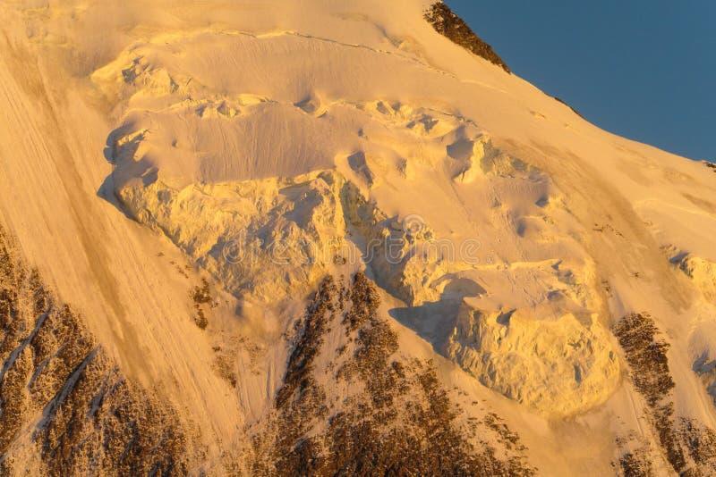 Наклон горы снега в Альпы на заходе солнца стоковые фотографии rf