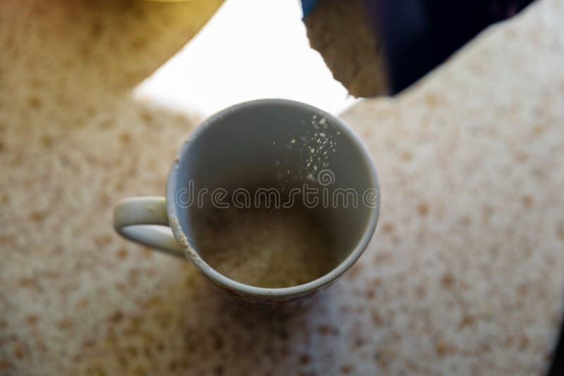 Наливая в чашку полноцветную муку для домашнего вегетарианского хлеба стоковое фото