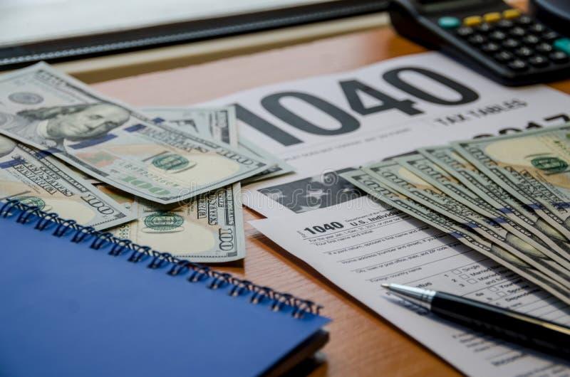 Налоговая форма 1040, доллары, голубая тетрадь, ручка, калькулятор на коричневом деревянном столе стоковые фотографии rf