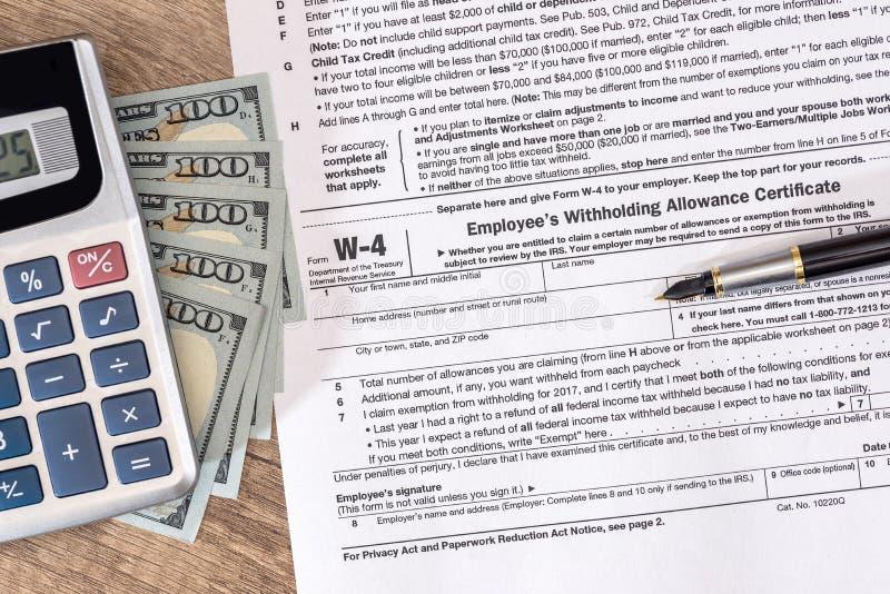 Налоговая форма W4 с деньгами и ручкой стоковые фото