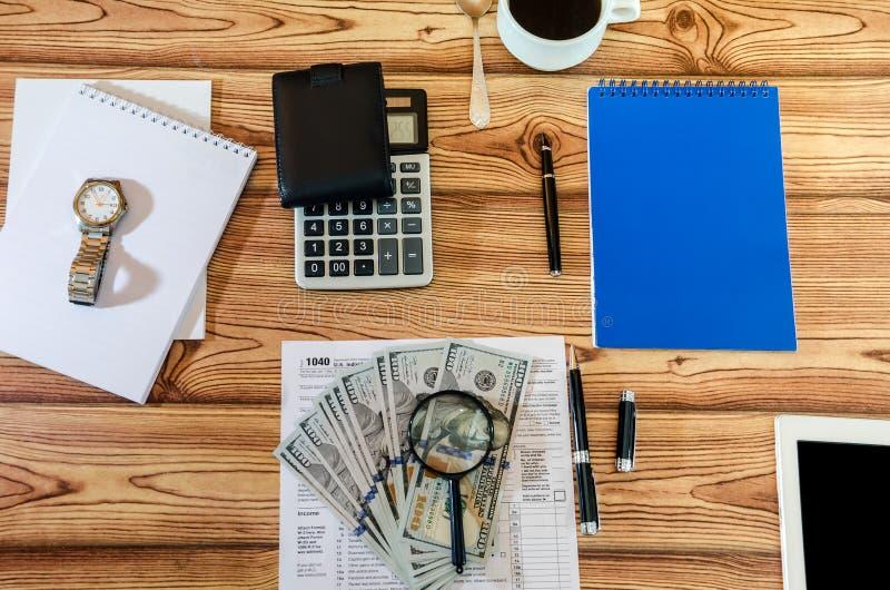 Налоговые формы 1040, блокноты, ручка, калькулятор и доллары на деревянном столе стоковые изображения rf