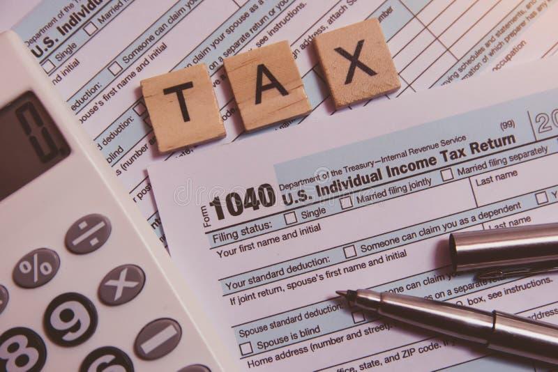 Налог с деревянными блоками алфавита, калькулятор, ручка на backgrounda налоговой формы 1040 стоковое изображение