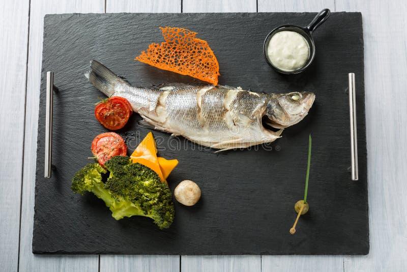 Намечайте плиту испеченного морского окуня с томатами, брокколи, прованского соуса ans стоковые фото