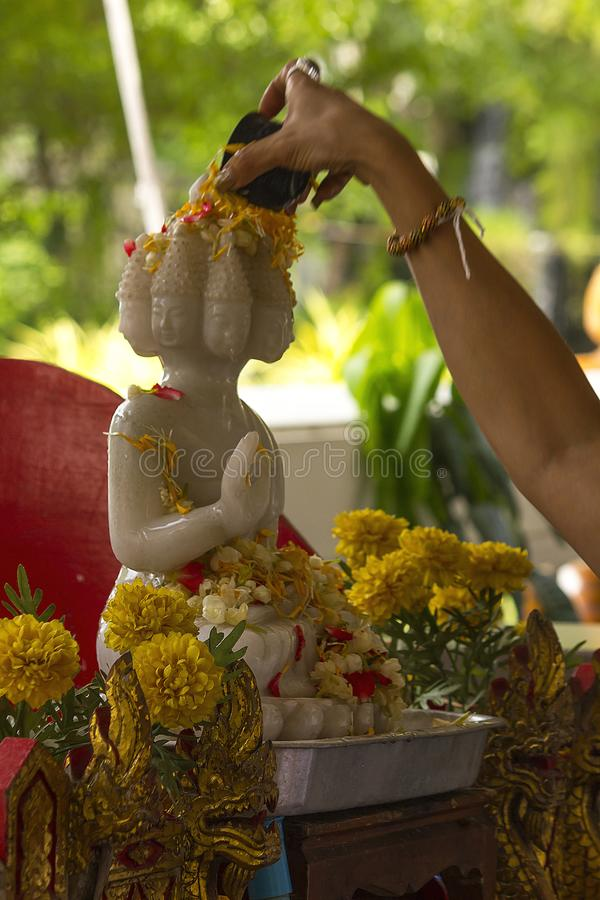 Намочите лить к статуе Будды белой, фестиваль Songkran стоковые фото
