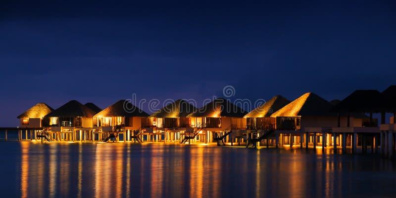 Намочите дома бунгал на заходе солнца, тропическом ландшафте стоковое фото rf