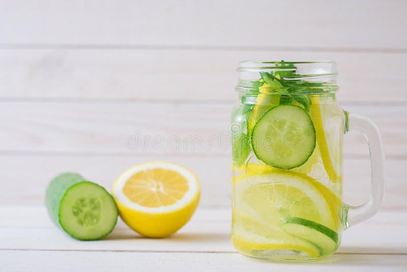 Намочите с лимоном и огурцом в стеклянной чашке стоковая фотография