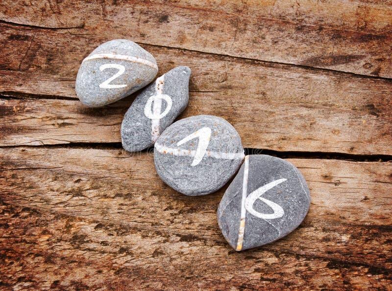 2016 написанное на lign камней на древесине стоковое изображение