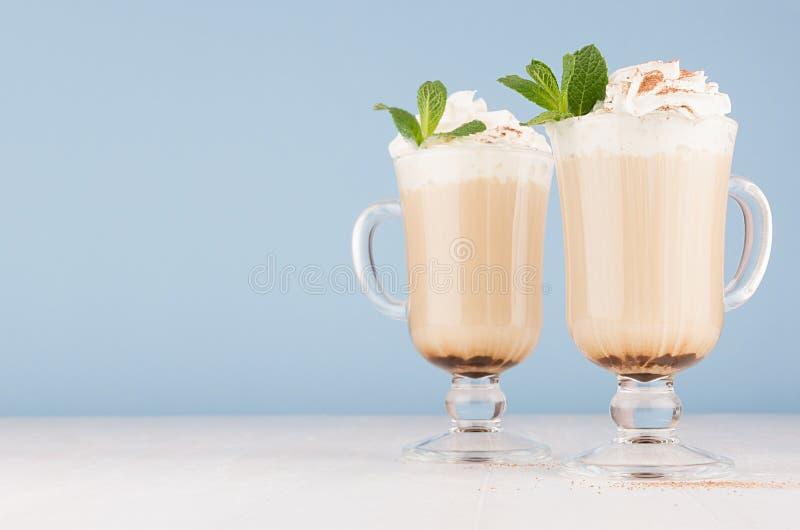 2 напитка кофе с взбитой сливк, зеленой мятой, бурым порохом на завтрак в стекле с ручкой в пастельном голубом интерьере стоковое изображение