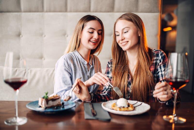 2 напитка пить цыпленоков и едят торты в кафе стоковые фотографии rf
