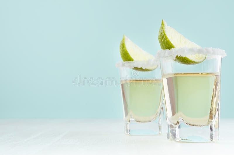 Напитки съемки золота лета свежие - текила в стопке с известкой, солью на крае на мягкой светлой пастельной голубой предпосылке стоковое изображение