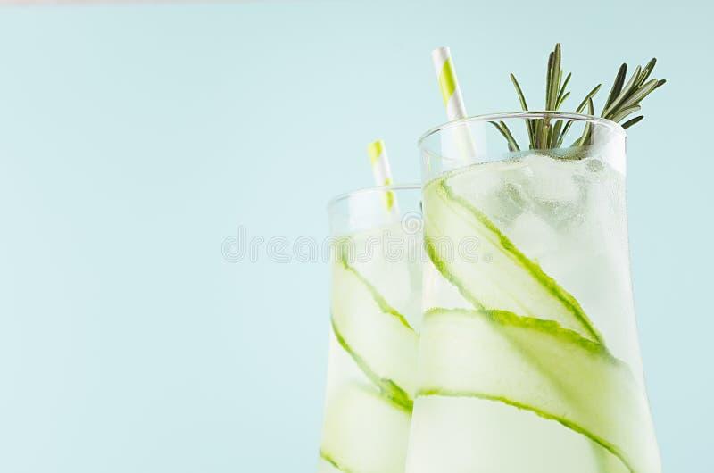 Напитки элегантного лета свежие с кубами льда, огурцом, розмариновым маслом, соломой на предпосылке цвета мяты моды пастельной, к стоковые фото