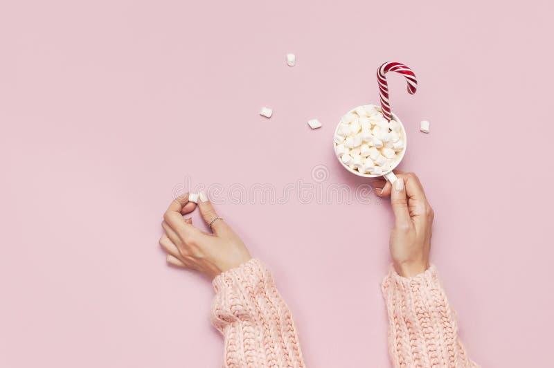 Напиток Нового Года рождества, белая кружка с зефирами в женских руках в связанной тросточке свитера и конфеты на розовой верхней стоковое изображение