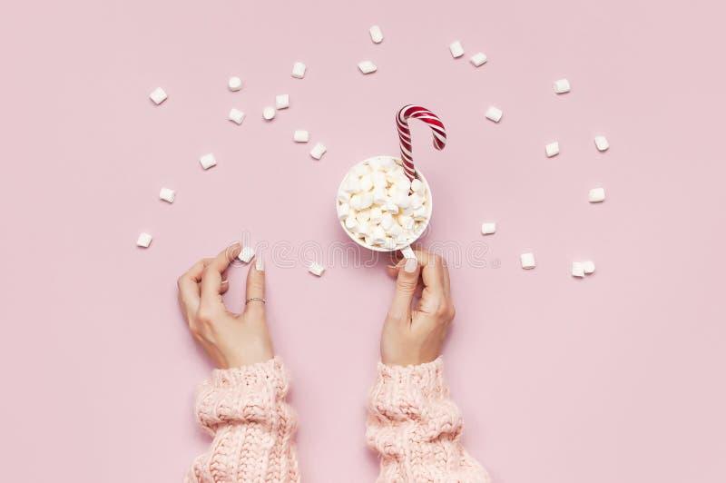 Напиток Нового Года рождества, белая кружка с зефирами в женских руках в связанной тросточке свитера и конфеты на розовой верхней стоковые изображения