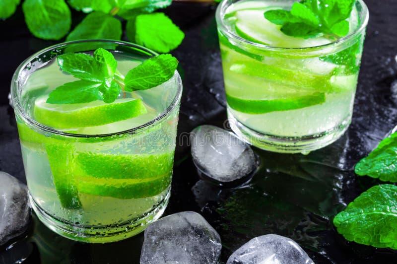 Напиток Mojito лета, с кубами известки, мяты и льда, на черной предпосылке с падениями воды стоковые фотографии rf
