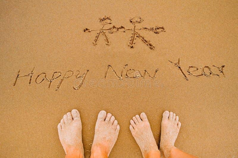 Напишите счастливый Новый Год на пляже к любовникам стоковые фото