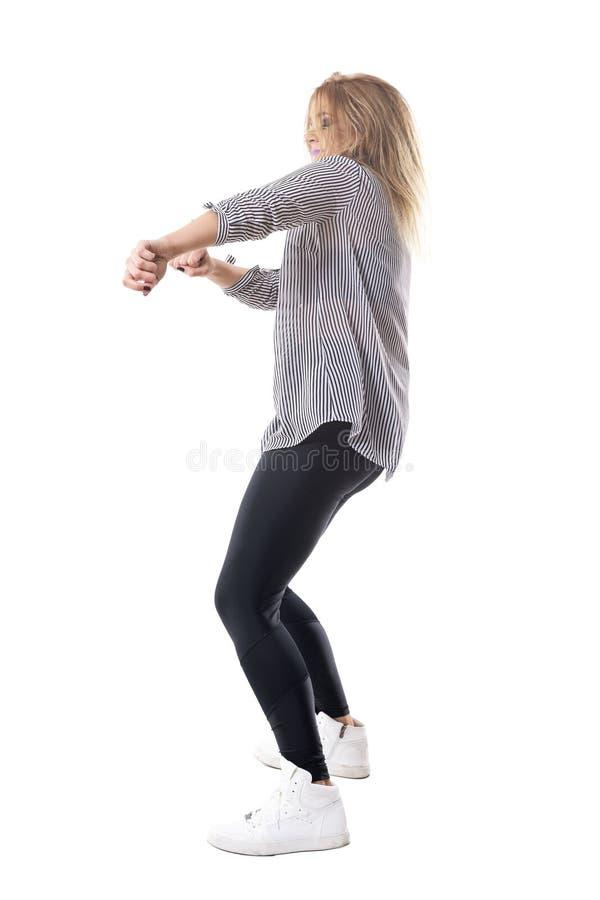 Напористые восторженные белокурые танцы женщины Взгляд со стороны стоковое изображение rf