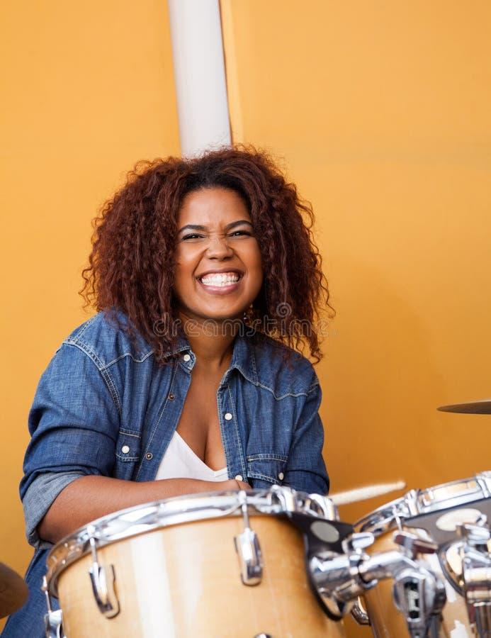 Напористый женский барабанщик выполняя в записи стоковые фото