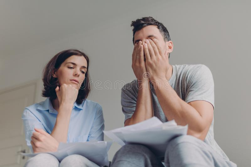 Напряженные пары семьи имеют проблемы задолженности, не способные для того чтобы оплатить их заем, управляют отечественным бюджет стоковая фотография rf