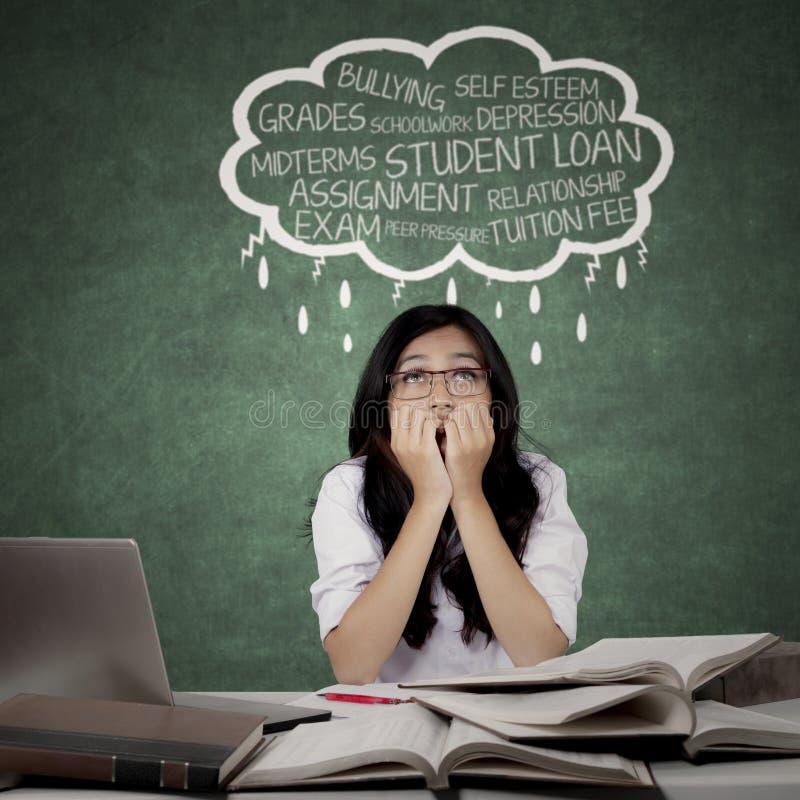 Напряжённая студентка думая ее проблемы стоковое изображение