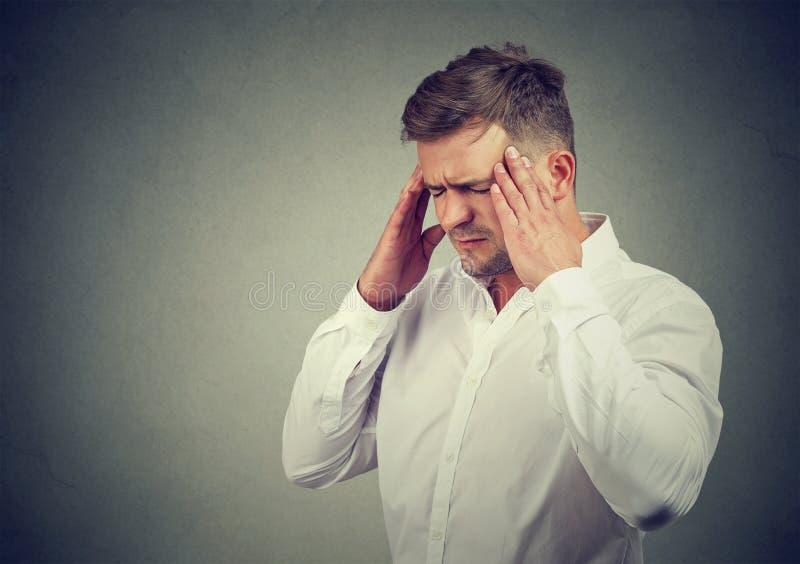 Напряжённый человек страдая с головной болью стоковая фотография rf