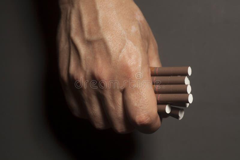 Наркомания табака Сигареты на руке человека стоковые изображения rf