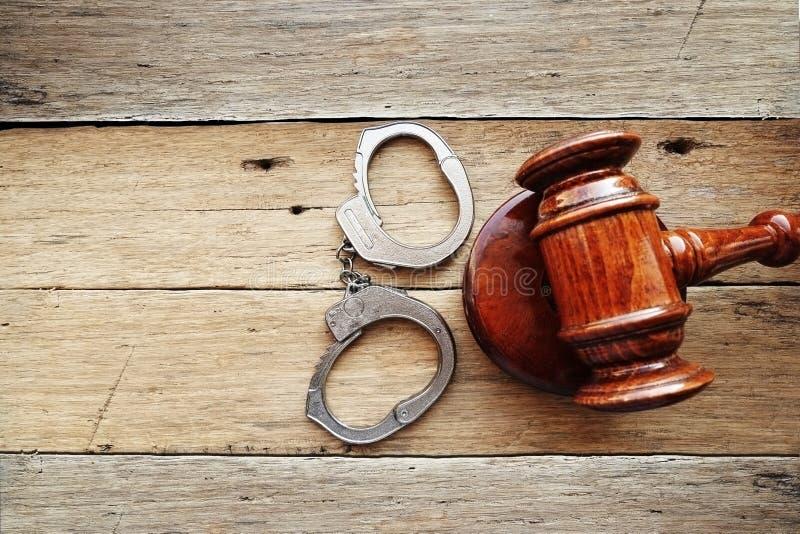Наручники и молоток судьи на деревянной предпосылке предлагая начинающ вердикт пробы злодеяния стоковые фотографии rf