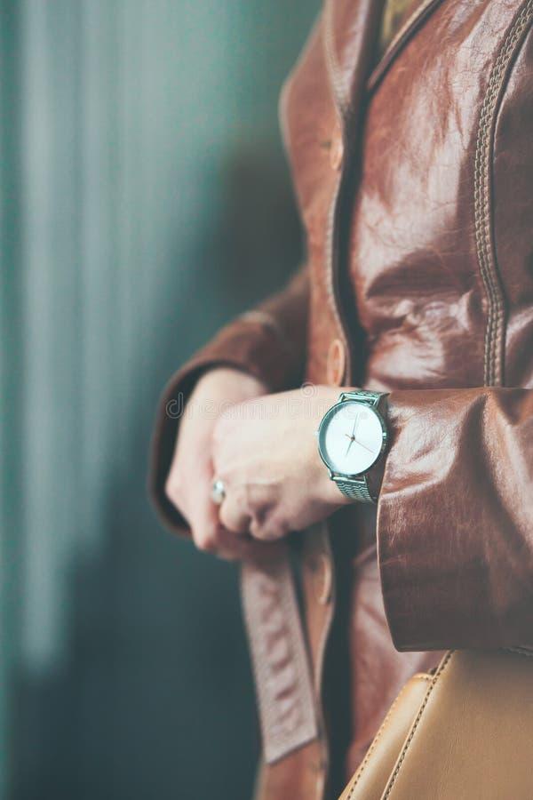 Наручные часы женщины нося серебряные и коричневое кожаное пальто держа l стоковое фото