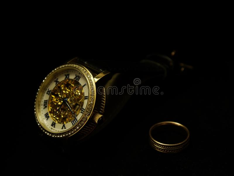 Наручные часы и кольцо людей на черном бархате стоковые фотографии rf