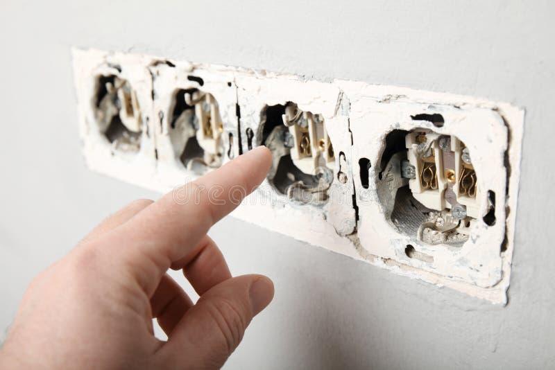 Нарушение электрических правил техники безопасности, поврежденное гнездо в стене стоковые изображения
