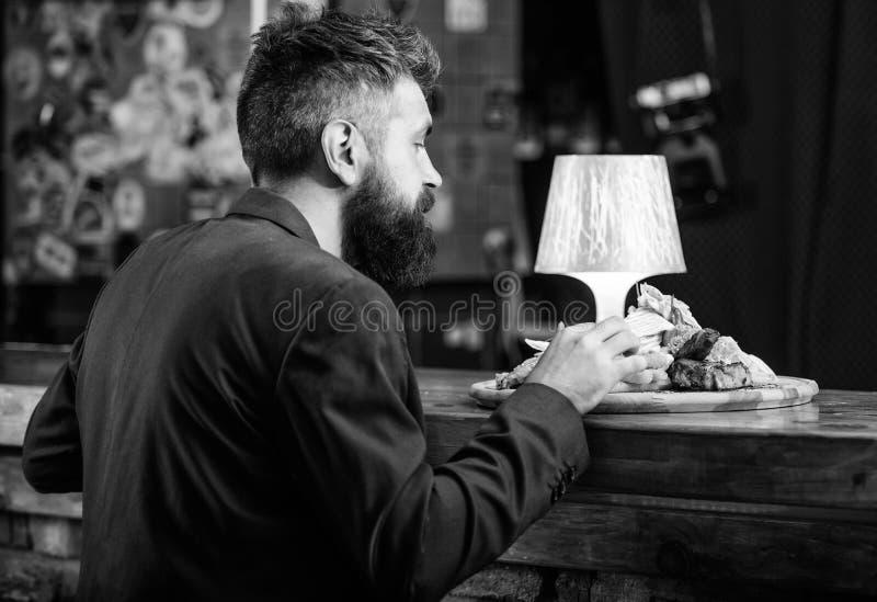 Насладитесь едой Клиент ресторана Костюм хипстера официальный сидит на счетчике бара Человек получил еду с зажаренными ручками ры стоковые фотографии rf