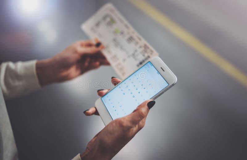 Насладитесь железнодорожной концепцией перехода Милая женщина используя smartphone пока стоящ в вокзале горизонтальный крупный пл стоковая фотография rf