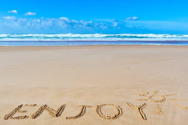 Насладитесь надписью на влажном песке пляжа под чертежом солнца и se стоковые фотографии rf