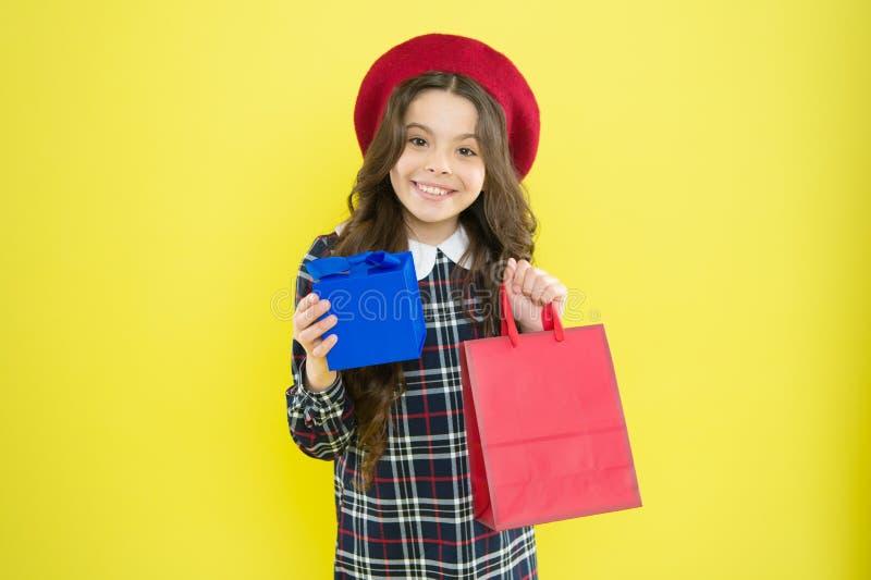 Наслаждаться ее подарком на день рождения Счастливый маленький ребенок получая ее подарок на день рождения на желтой предпосылке  стоковые фотографии rf