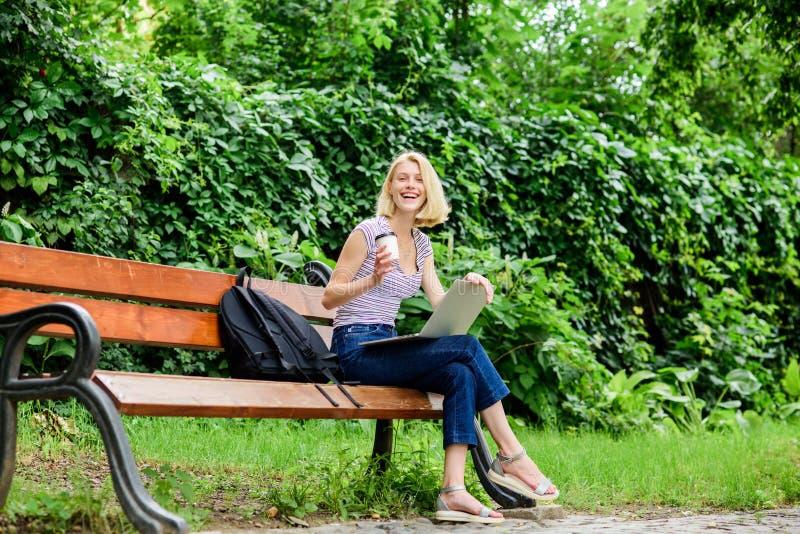 Наслаждаться жизнью университета работа девушки на ноутбуке лето онлайн Диаграмма утра кофе напитка девушки, который нужно пойти  стоковые фото