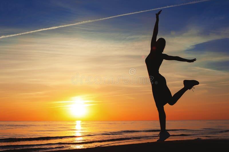 Наслаждаться заходом солнца лета Жизнерадостные танцы силуэта женщины дальше стоковая фотография rf