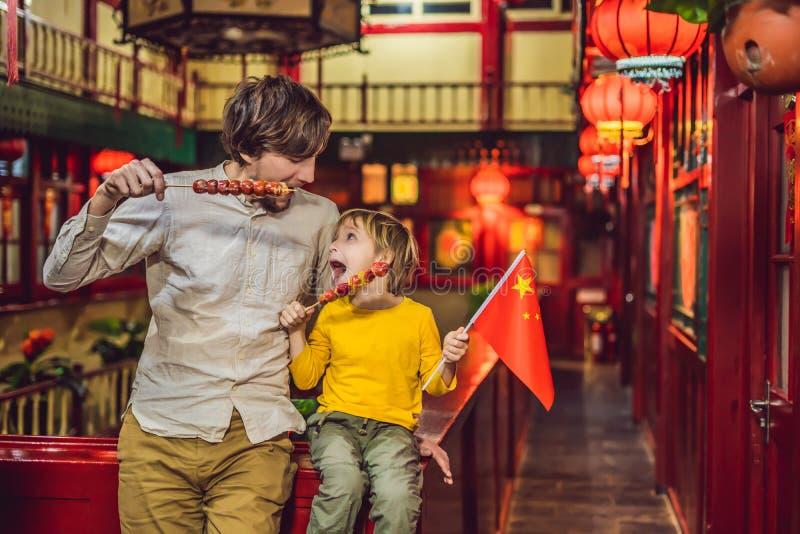 Наслаждаться каникулами в Китае Счастливые туристы папа и сын с китайским флагом и с плодами традиционного китайского candied стоковые изображения
