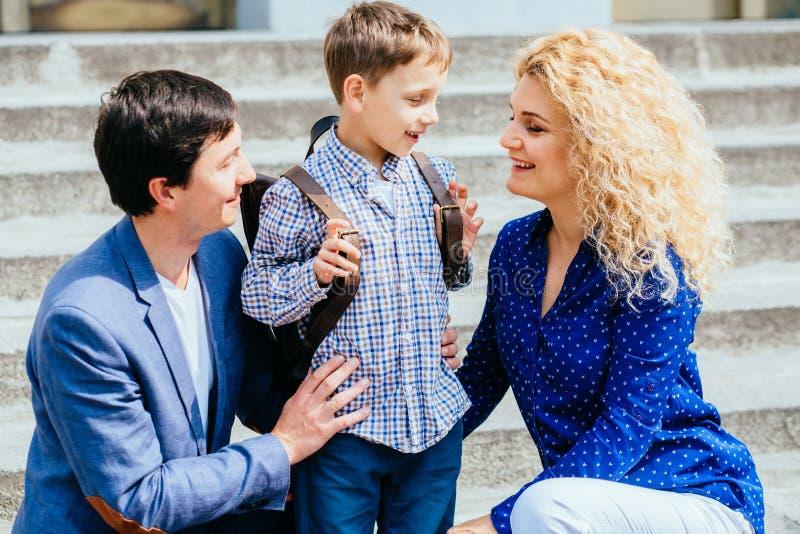 Наслаждаться концепцией семьи Мать и папа отправляя их первый раз мальчика зрачка ребенка studing в школу над лестницами дальше стоковые изображения