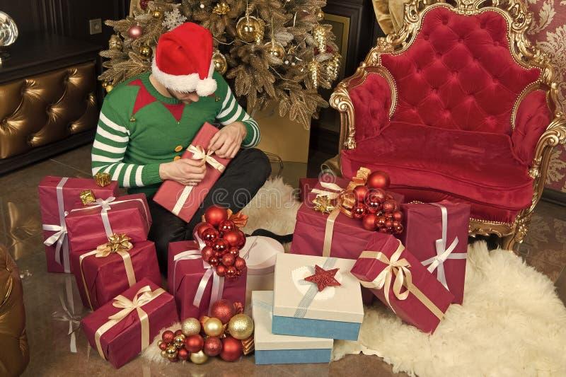Наслаждаться рождеством Человек в подарках на рождество владением шляпы santa Гай празднует xmas дома Подарки рождества доставки стоковое изображение rf