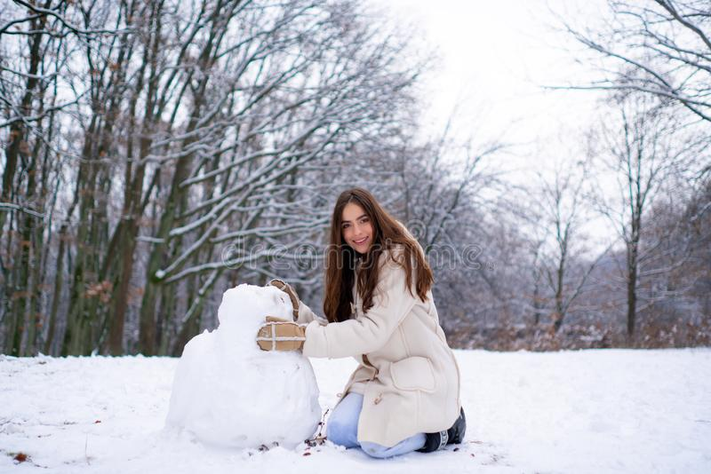 Наслаждаться wintertime природы Женщина зимы счастливая Красивая девушка в лесе зимы в белизне вниз с куртки стоковые фотографии rf