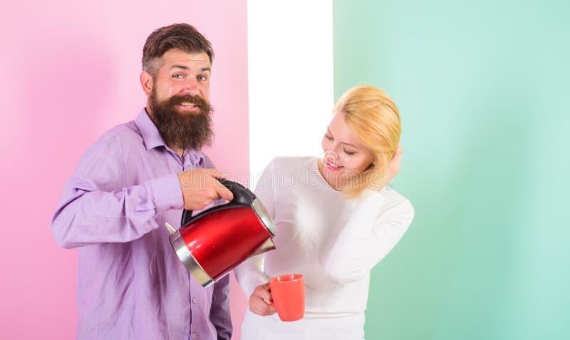 Наслаждающся славным утром совместно Человек с электрическими чайником и женщиной с кружкой готовой для того чтобы выпить кофе ут стоковые изображения