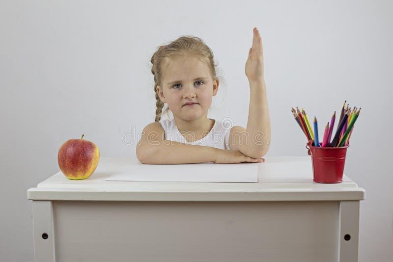 Насмешка вверх по дню девушки первому школы сидя на ее столе и держа ее руку вверх стоковая фотография rf