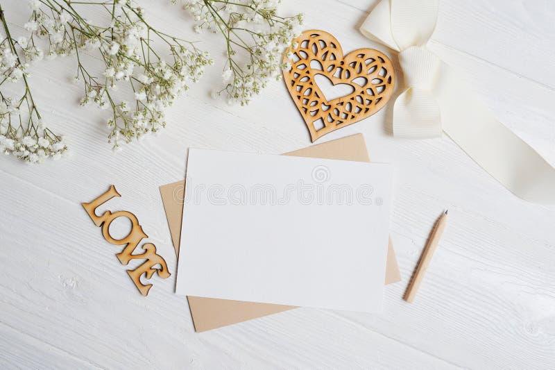 Насмешка вверх по письму с коробкой влюбленности в форме сердца лежит на деревянной белой таблице с цветками гипсофилы, приветств стоковые фото