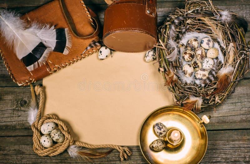 Насмешка года сбора винограда вверх на деревенской деревянной доске Подсвечник, яичка внутри гнезда, тетрадь, катушка веревочки,  стоковое фото