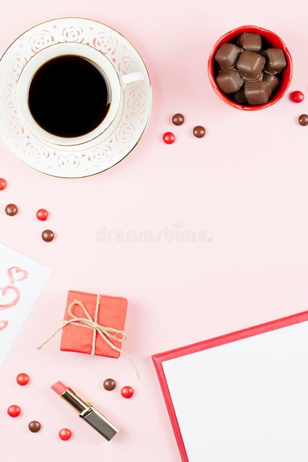 Насмешка дня ` s валентинки вверх с питьем кофе, giftbox, конфетами на предпосылке пастельного пинка, плоском положении стоковые изображения rf