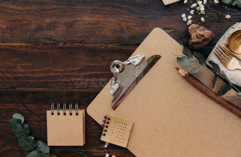 Насмешка доски сзажимом для бумаги вверх с винтажными украшениями столового прибора и свадьбы на деревянной предпосылке стоковое фото rf