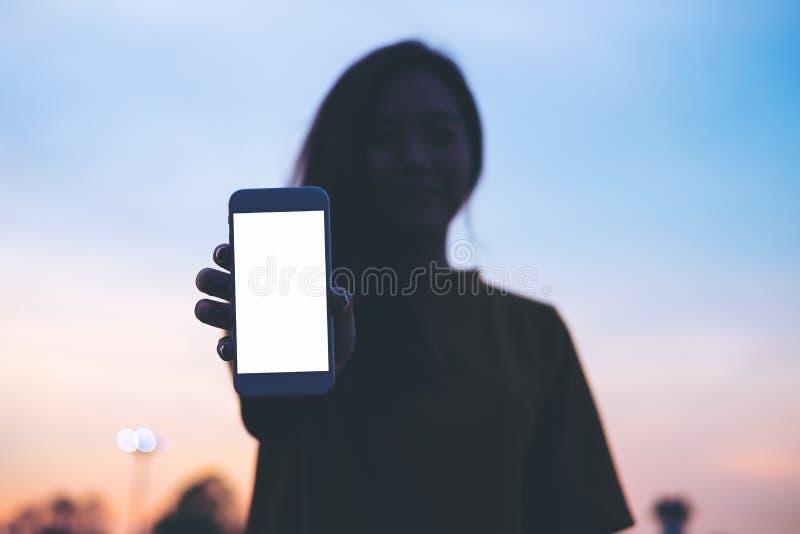 Насмешка показа женщины вверх по белому экрану умного телефона с небом перед предпосылкой захода солнца и космосом экземпляра стоковые фото