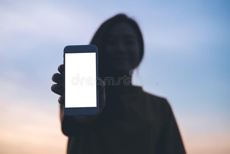 Насмешка показа женщины вверх по белому экрану умного телефона с небом перед предпосылкой захода солнца и космосом экземпляра стоковая фотография rf
