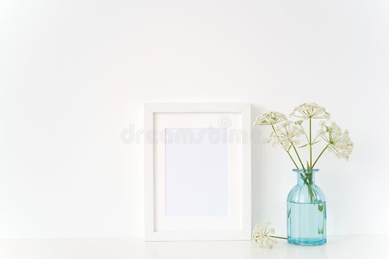 Насмешка рамки портрета a5 милого лета белая вверх с одичалым хозяином в прозрачной голубой вазе стоковое изображение